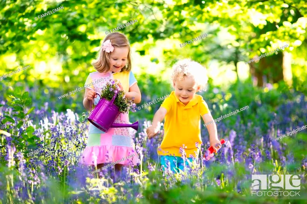 Stock Photo: Kids gardening. Children play outdoors in bluebells meadow. Little girl and boy, brother and sister, work in the garden, planting bluebell flowers.