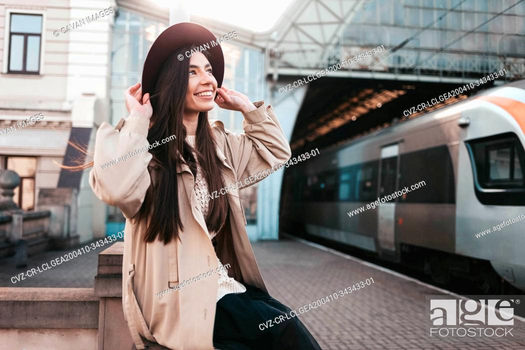 Stock Photo: Smiling girl in hat at train station waiting for train departure.