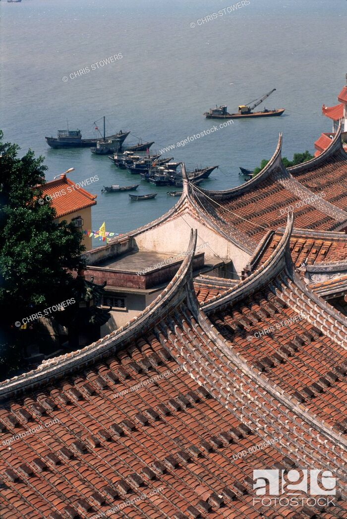 Imagen: China, Fujian, Meizhou Island, tiled gabled rooftops overlooking moored fishing boats on the shore, elevated view.