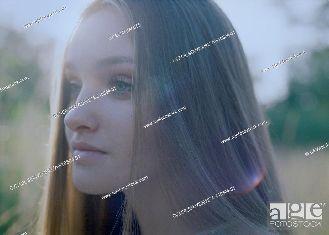Stock Photo: Close-up of the face of a young woman at dusk in the forest.
