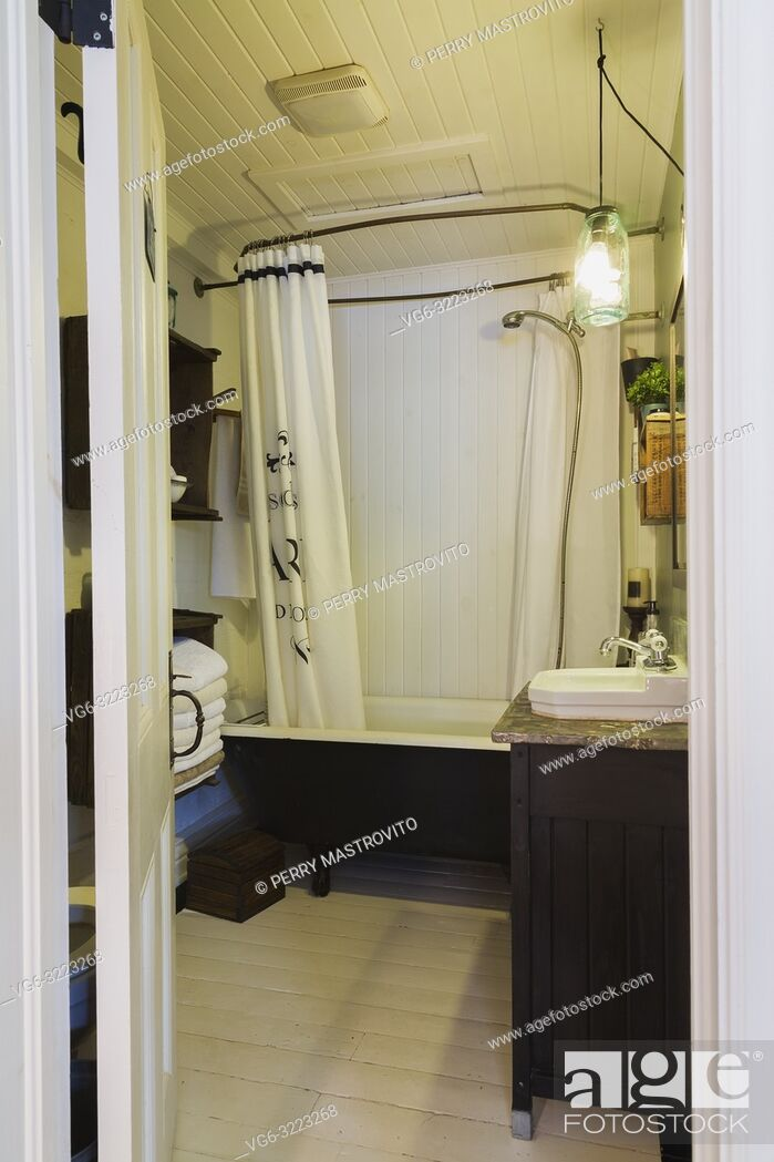 Stock Photo: Bathroom with freestanding bathtub and white painted pinewood floor inside an old 1862 cottage style home.