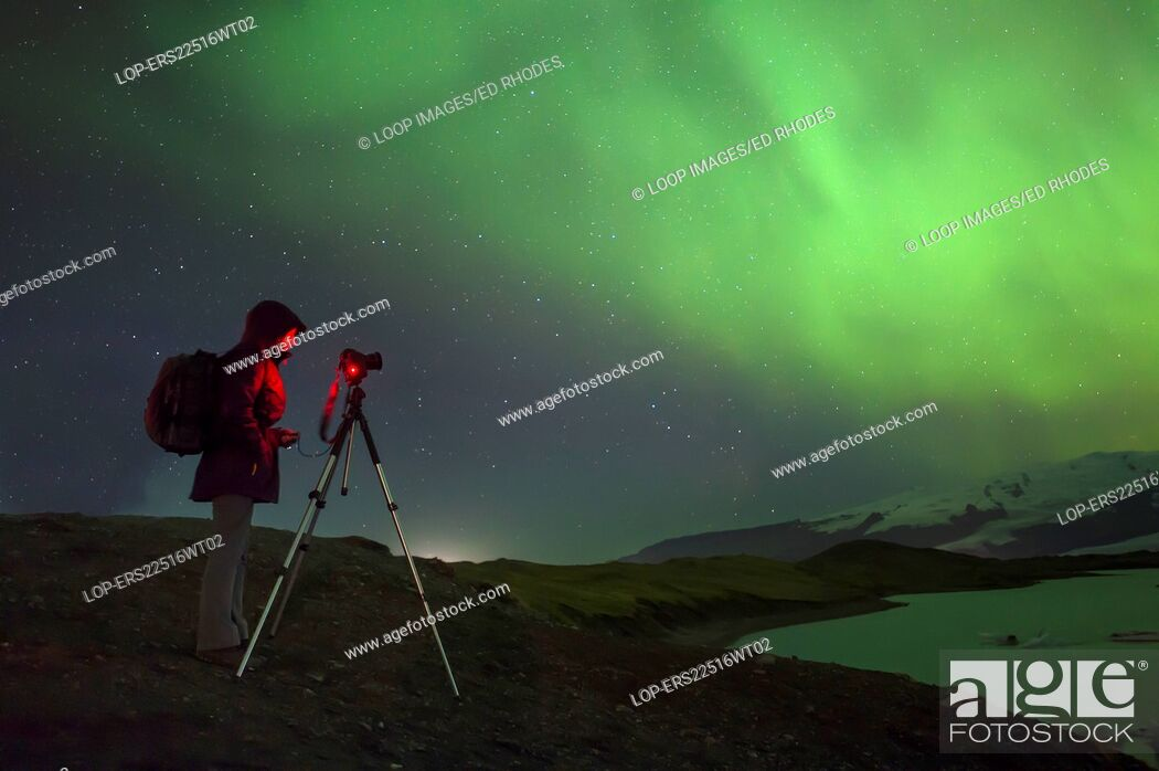 Photo de stock: A photographer photographing the Aurora at Jokulsarlon Iceberg Lagoon.