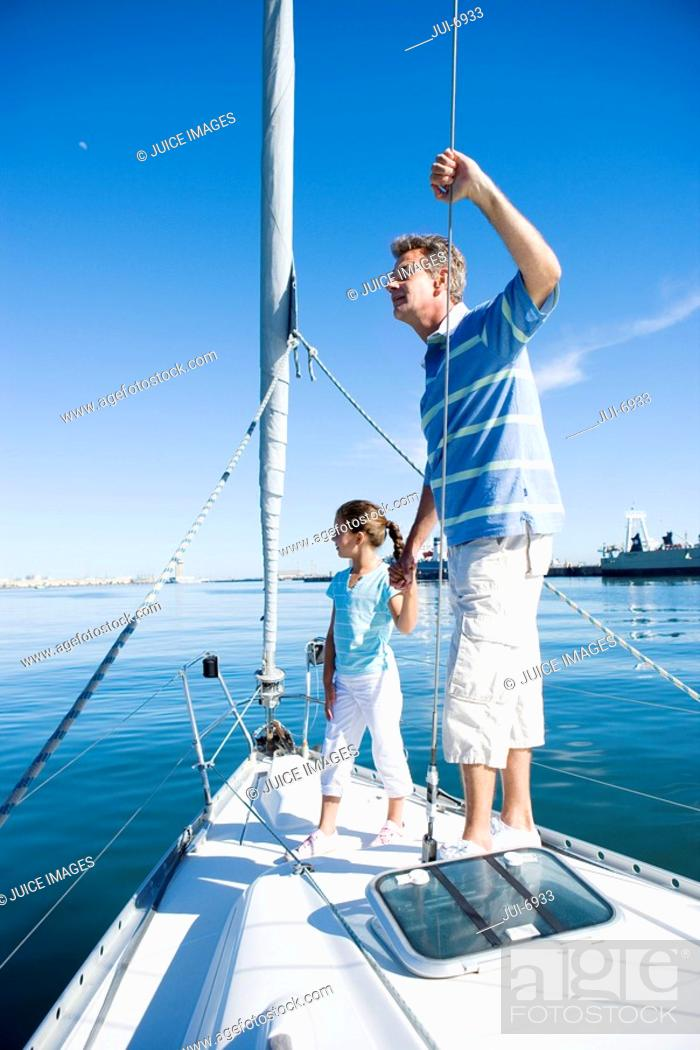 Stock Photo: Father and daughter 8-10 standing at bow of sailing boat, holding hands, man leaning on rigging, looking at sea, side view.