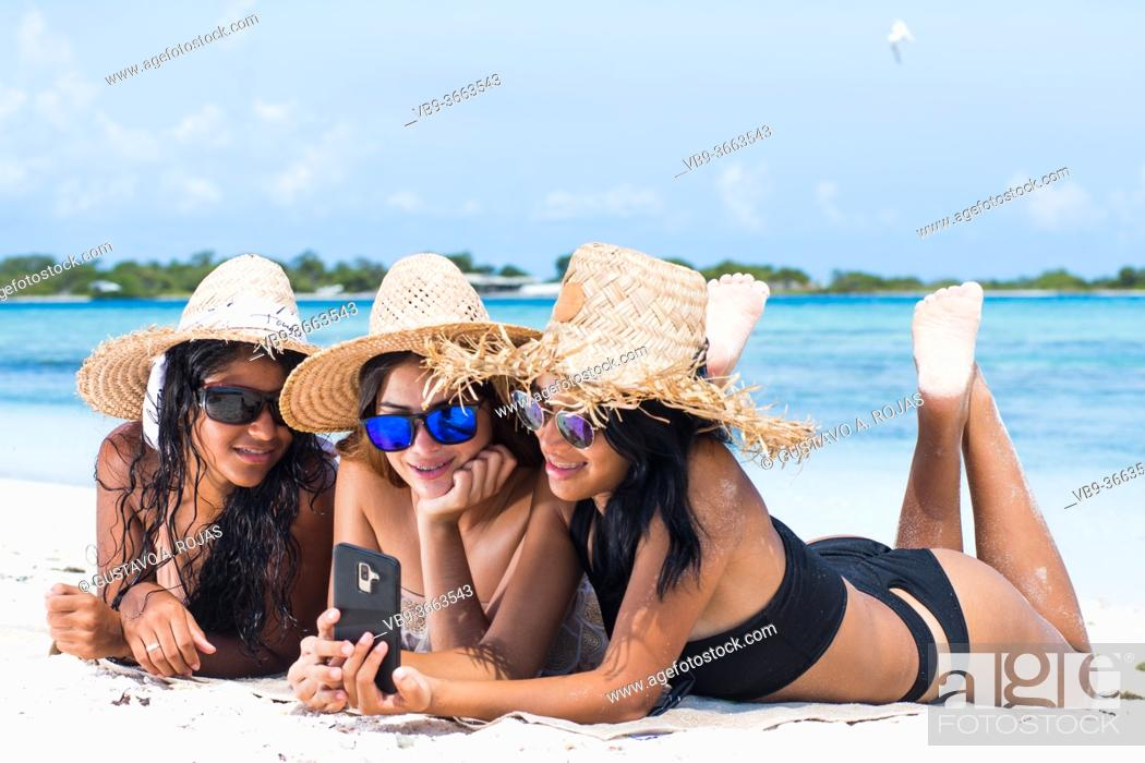 Stock Photo: Three happy latin girls friends in summer clothes have fun and taking a selfie at caribbean beach at LosRoques Venezuela.