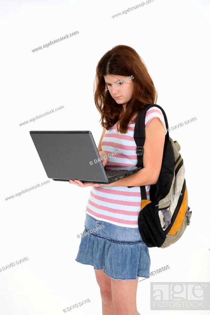 Stock Photo: Portrait of Caucasian teen getting ready for school and working on a laptop.