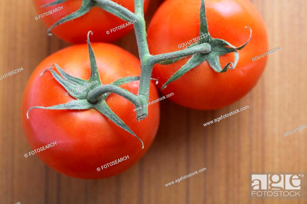 Stock Photo: Close-up of tomatoes on vine.