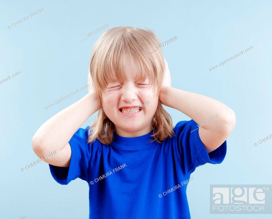 Stock Photo: upset boy with long blond hair covering his ears as protection - isolated on blue.