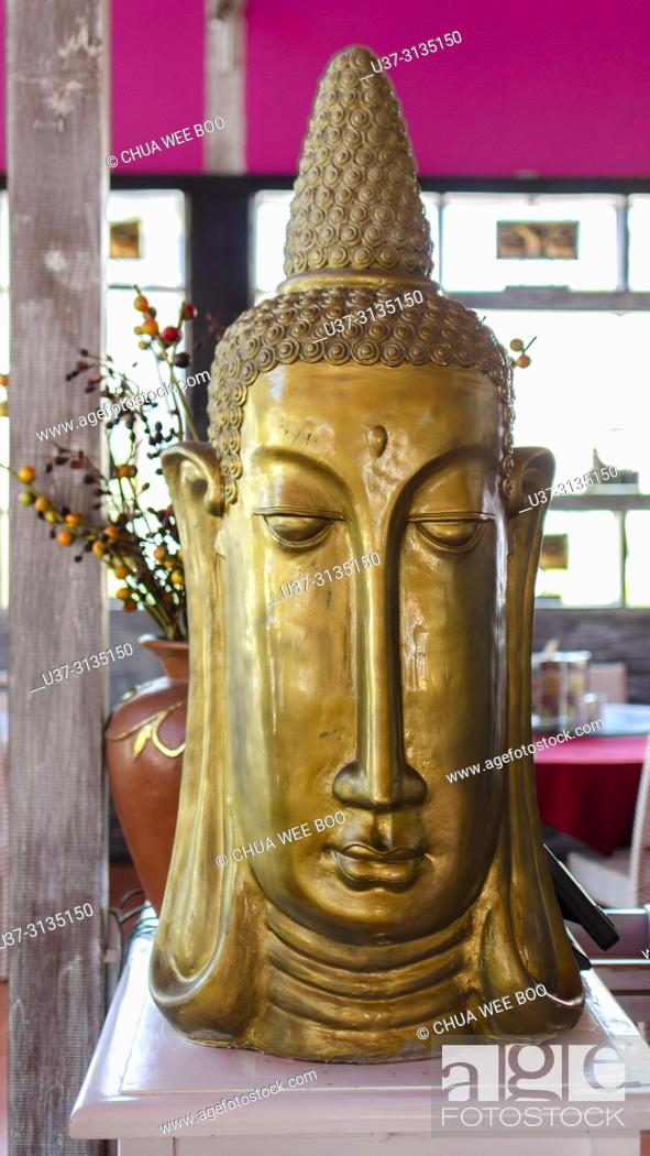 Stock Photo: Gold Budhha face placed at a restaurant in Seminyak Street, Bali.