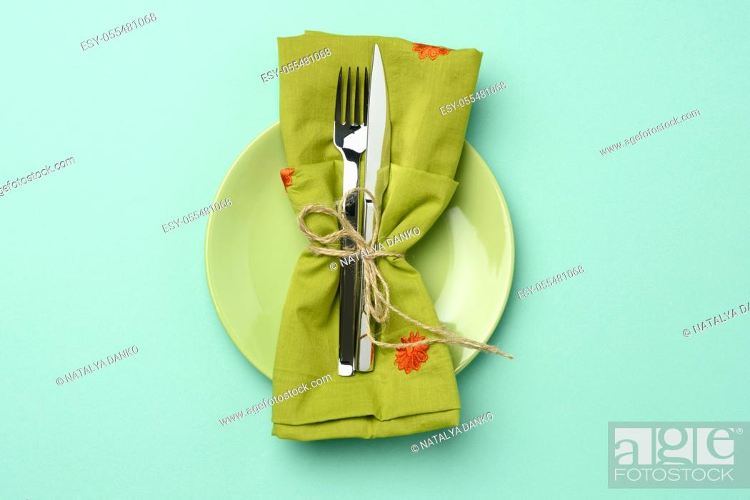Stock Photo: empty round green ceramic plate and metal fork and knife, green background, top view.