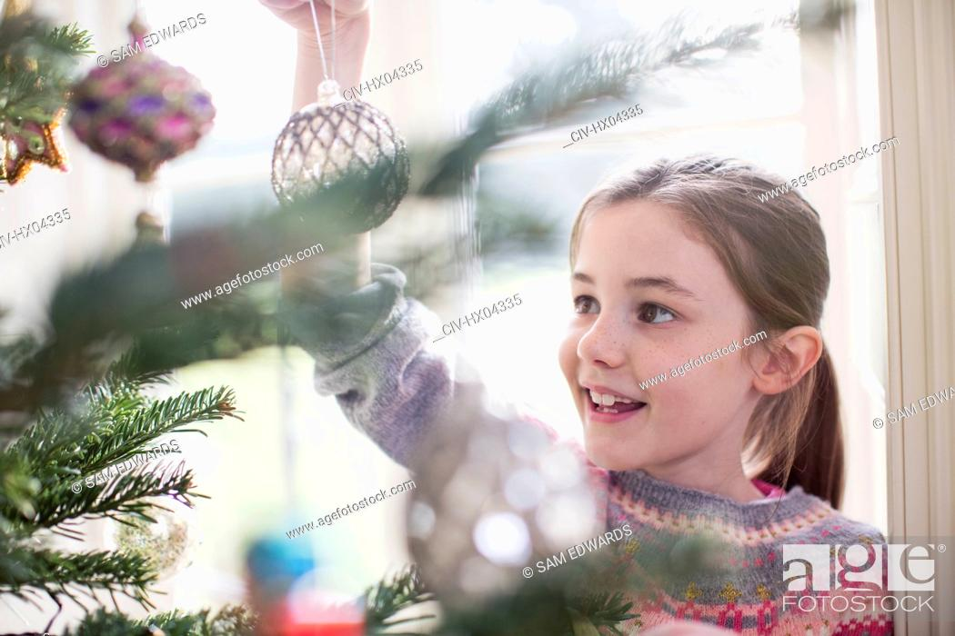 Stock Photo: Girl decorating, hanging ornament on Christmas tree.