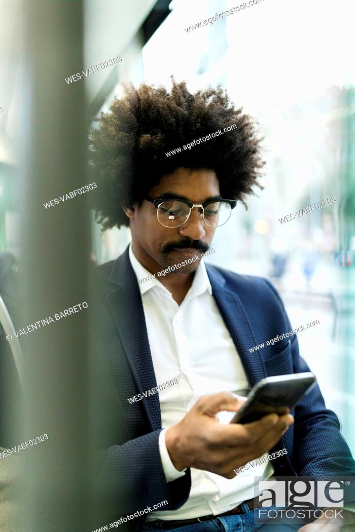 Stock Photo: Spain, Barcelona, businessman in a tram using cell phone.