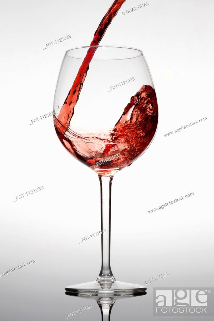 Stock Photo: Red wine being poured into a glass.