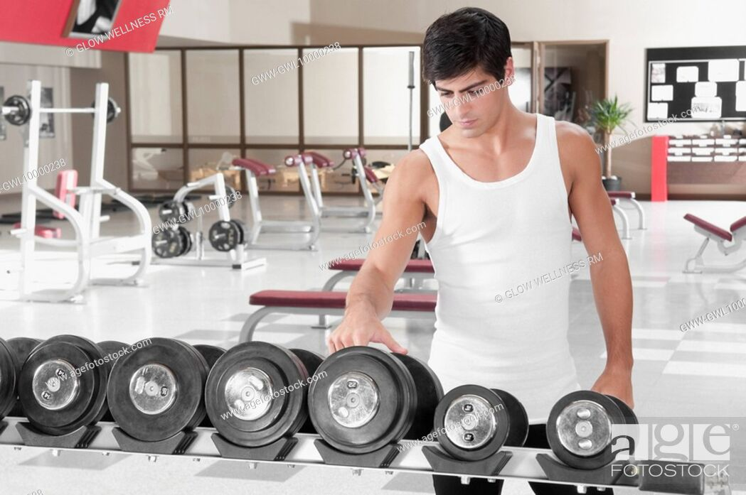 Imagen: Man choosing dumbbells in a gym.
