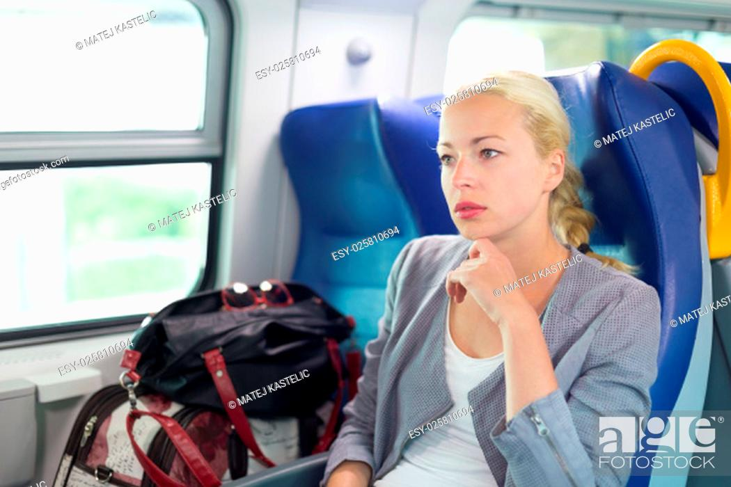 Stock Photo: Blonde caucasian business woman traveling by train. Business travel concept.