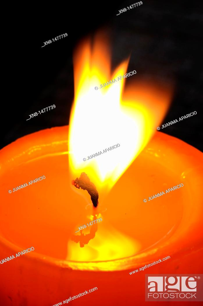 Stock Photo: Detail of a candle flame with waving in the air on a dark background.