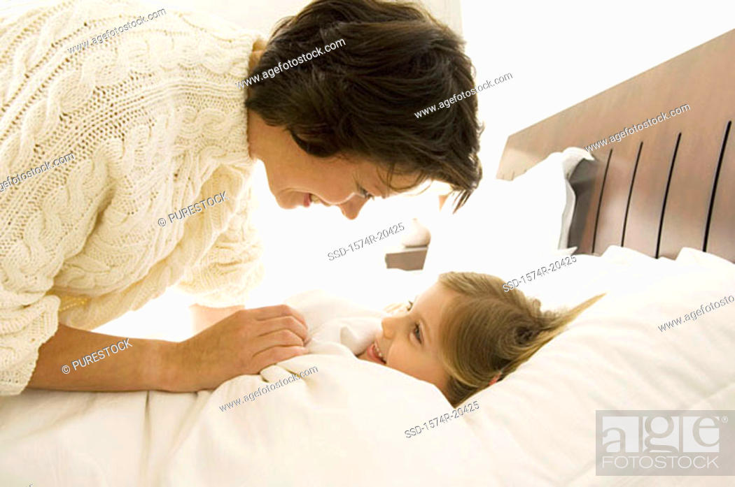 Stock Photo: Close-up of a mother bending over her daughter lying on the bed.