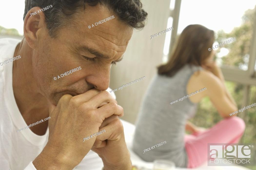 Stock Photo: Couple in bedroom, woman in background, indoors.