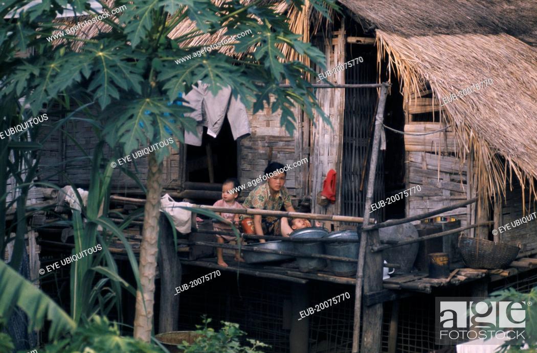 Mother Bathing Children Outside Stilt House Stock Photo