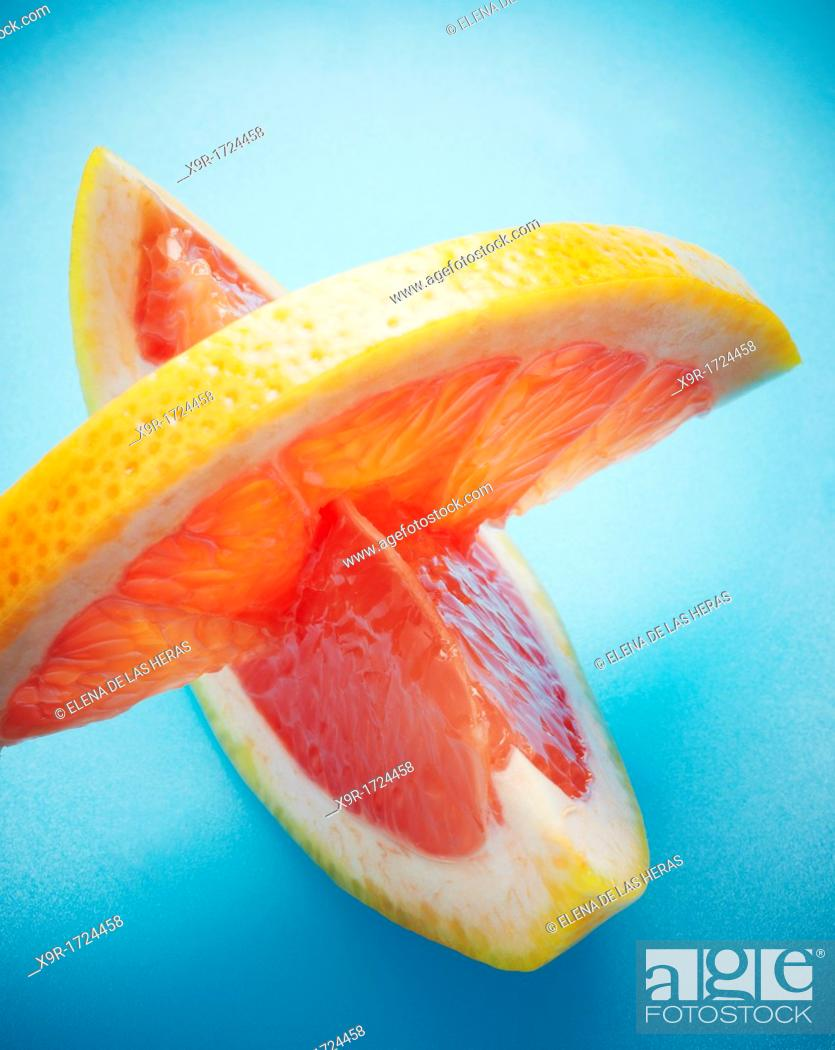 Stock Photo: Grapefruit pieces in blue background.