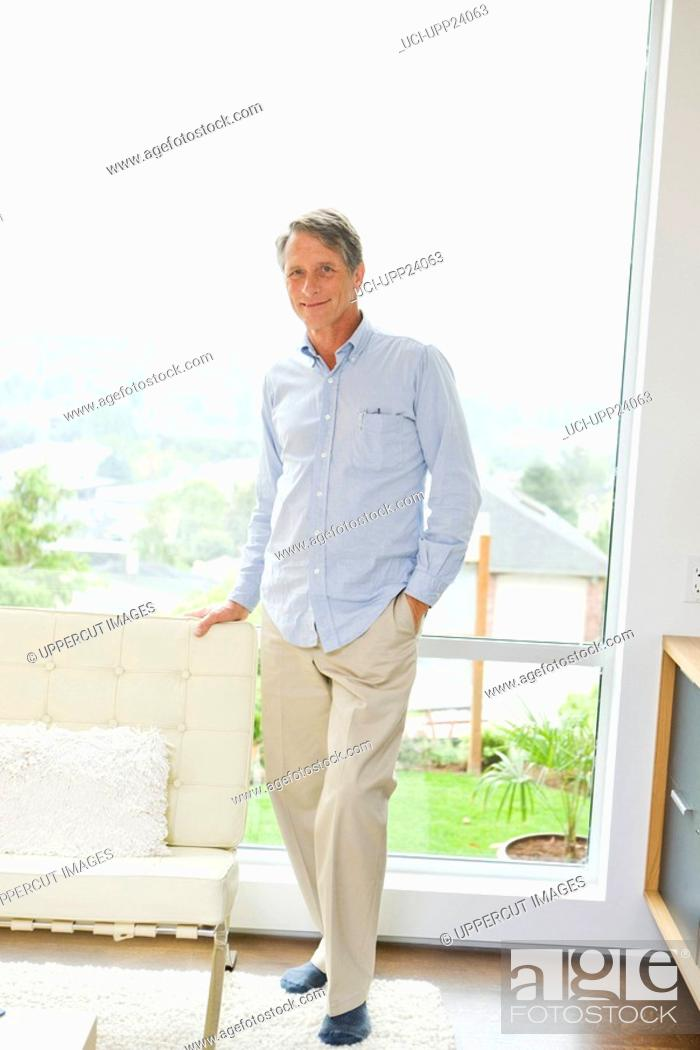 Stock Photo: Portrait of man standing in front of living room window.