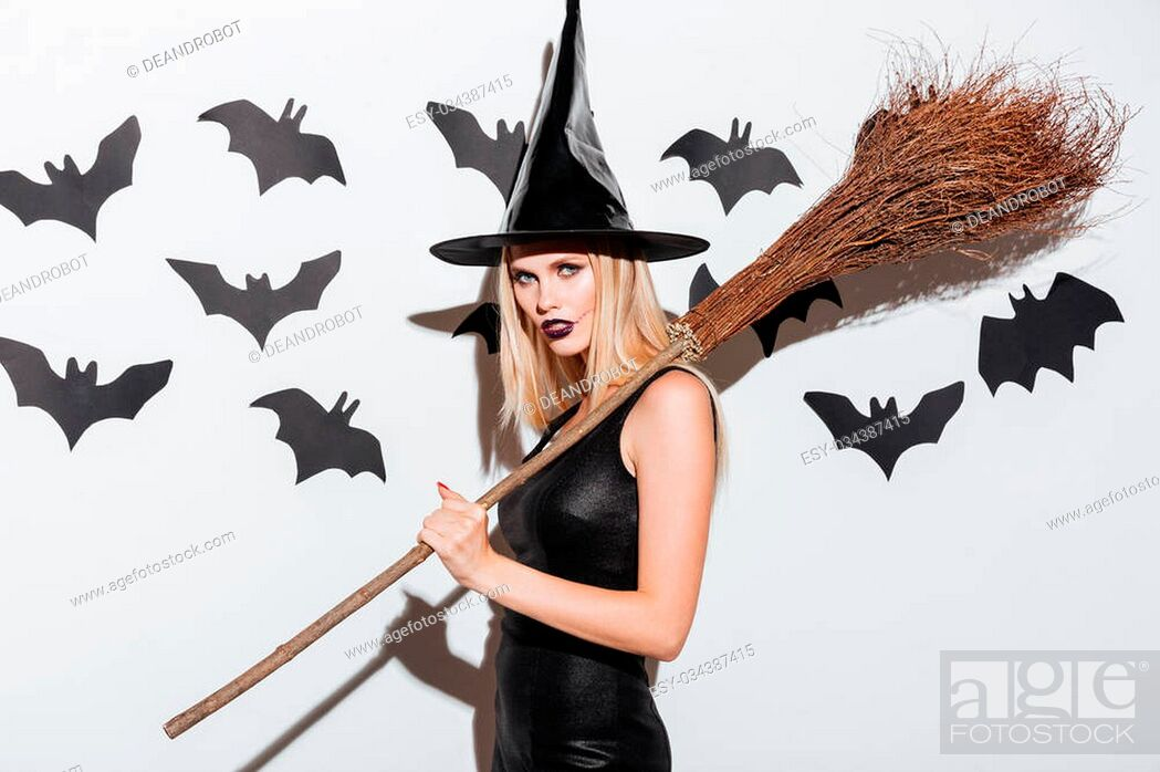 Stock Photo: Portrait of beautiful young woman in black witch halloween costume with broom over white background.