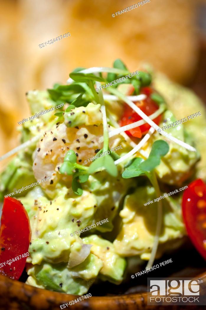 Photo de stock: fresh avocado and shrimps salad with nachos on side.