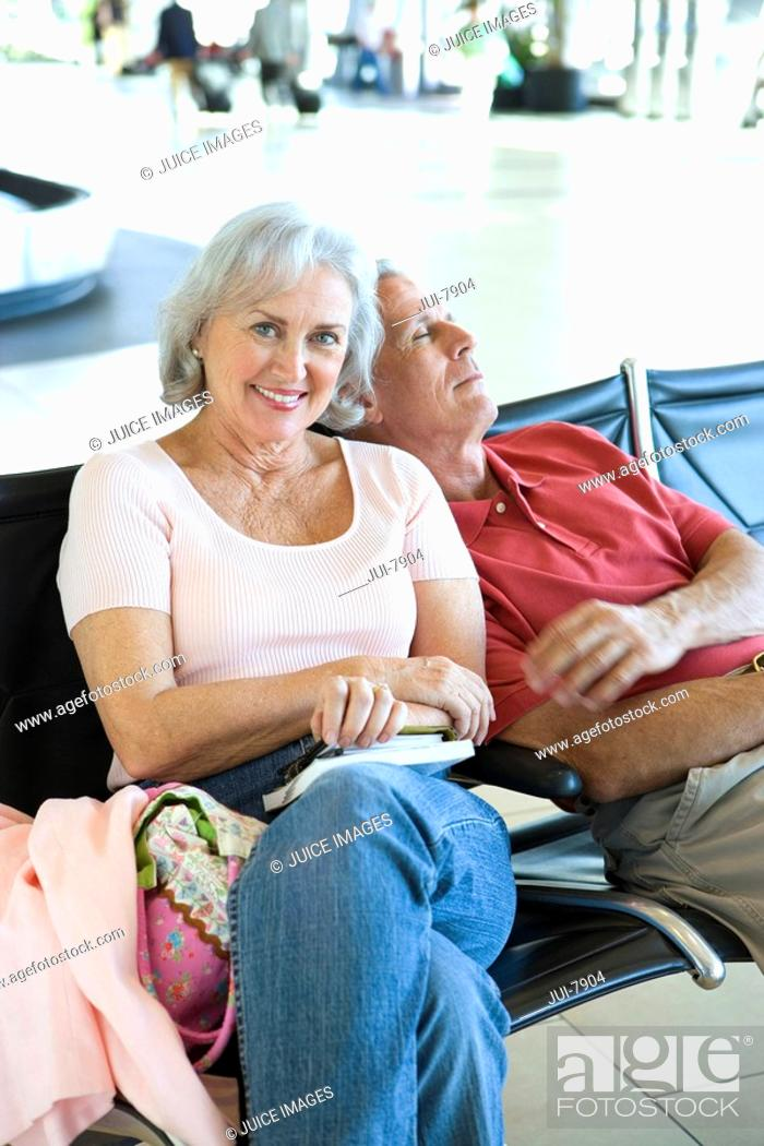 Stock Photo: Senior couple sitting in airport departure lounge, man leaning on womanÔÇÖs shoulder, sleeping, woman smiling, portrait.