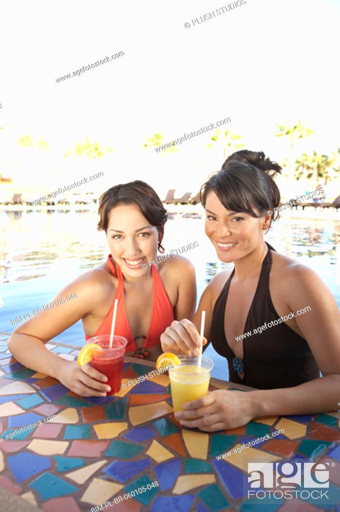 Stock Photo: Two Hispanic women at hotel pool bar, Los Cabos, Mexico.