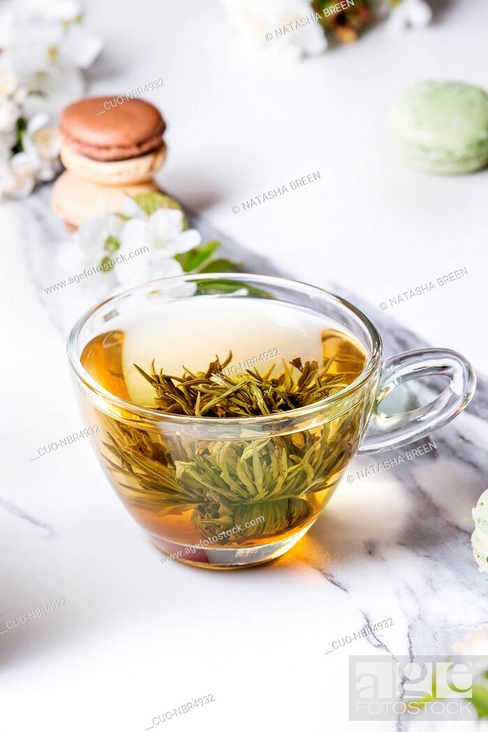 Stock Photo: Glass cup of hot green tea with french dessert macaroons, spring flowers white magnolia and cherry blooming branches over white marble texture background.