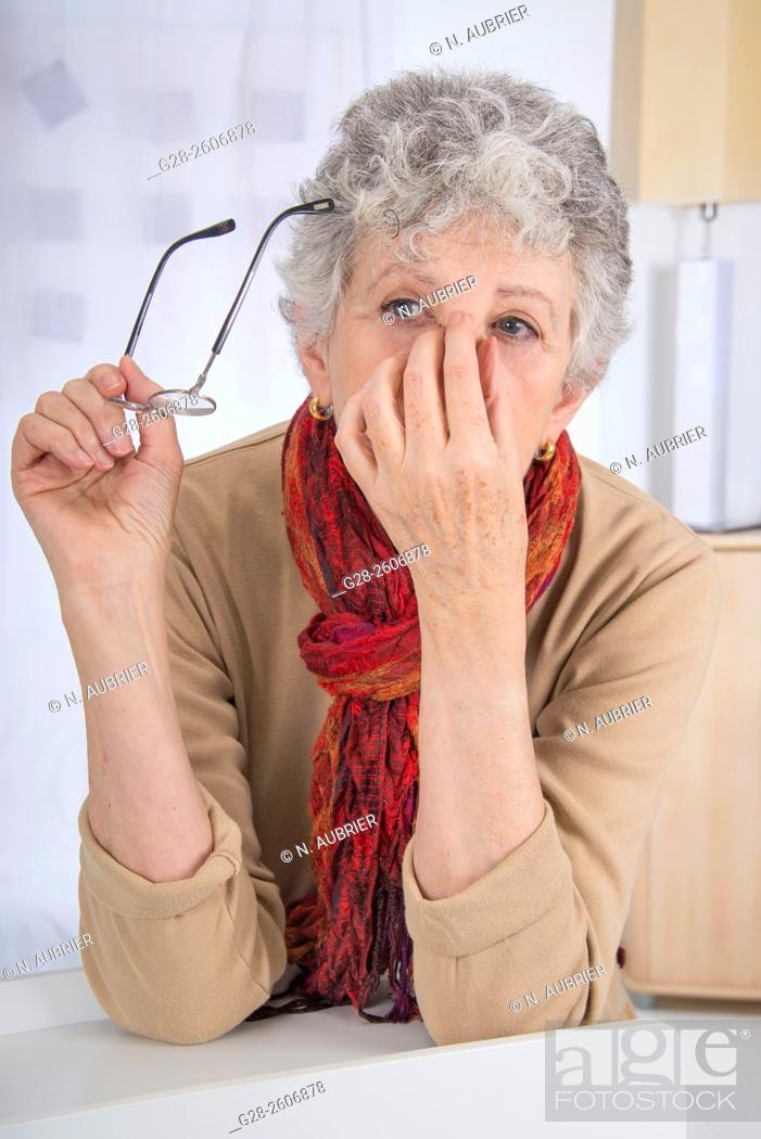 Stock Photo: Senior woman with grey hair, holding top of her nose with one hand to relieve sinusitis and headache, with one hand the other hand is holding her glasses.