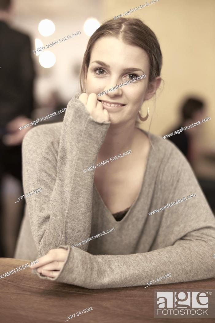 Stock Photo: Young woman in café, Munich, Germany.