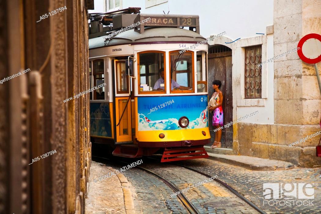 Stock Photo: Tram 28 -known by the Portuguese as the electric tram - is going down Rua Sao Vicente in Alfama district, moving toward the lower area of Lisbon, Portugal.