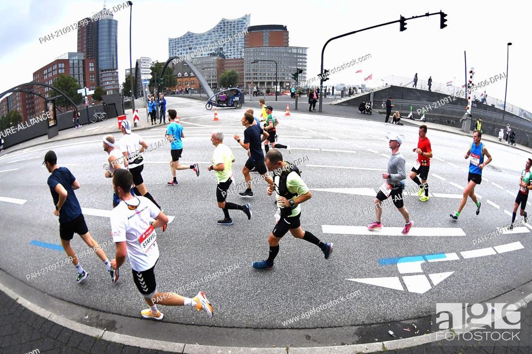 Stock Photo: 12 September 2021, Hamburg: Athletics: Marathon: Marathon runners in front of Speicherstadt and Elbphilharmonie. Photo: Michael Schwartz/dpa.