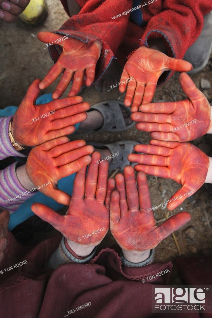 Stock Photo: children coloring their hand red with henna.