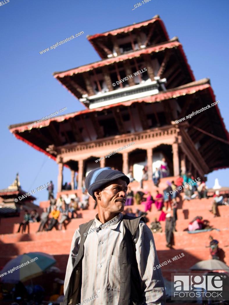 Imagen: Pedestrians walk and travel by cart down a street in Kathmandu, Nepal.