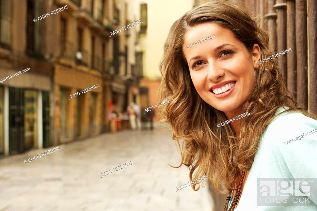 Stock Photo: Young woman standing outside buildings in street portrait.