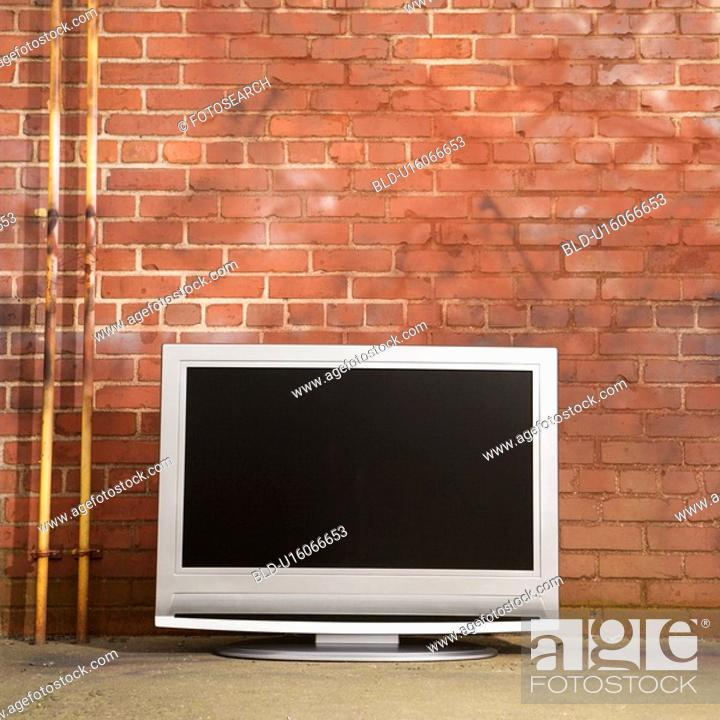 Stock Photo: Flat panel television set in front of red brick wall.
