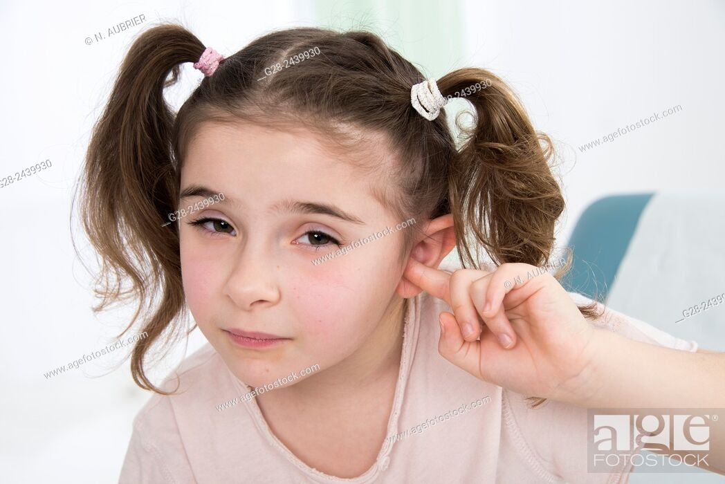 Stock Photo: Little girl with bunches stopping her ear with her finger sitting on a medical couch.