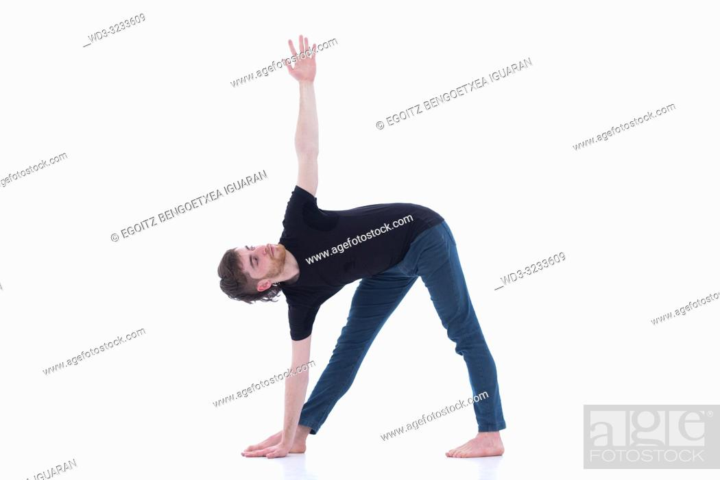 Imagen: Casual dressed young adult man making yoga exercises on white background.