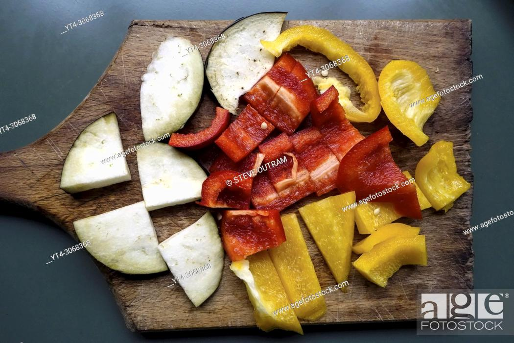 Stock Photo: Sliced Aubergine and Bell Peppers on Chopping Board.