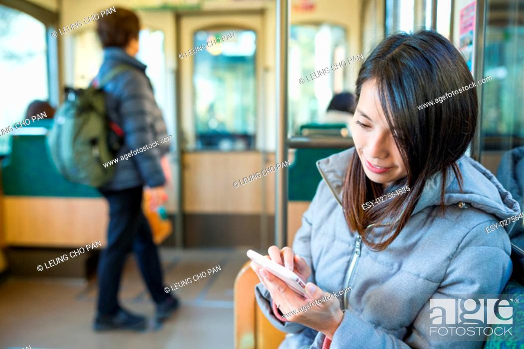 Stock Photo: Woman using mobile phone inside train compartment.