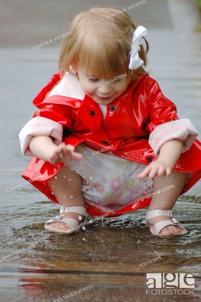 Stock Photo: Close up of toddler girl playing in puddle.
