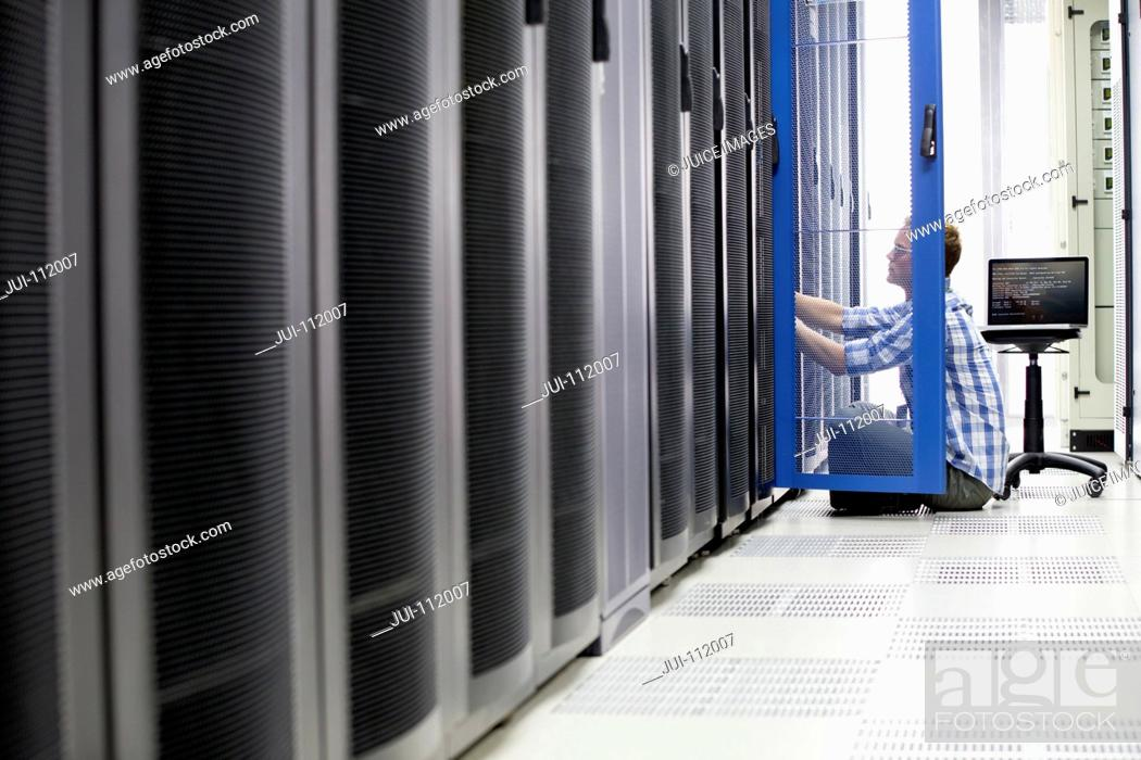 Stock Photo: Technician with laptop checking server in data centre.