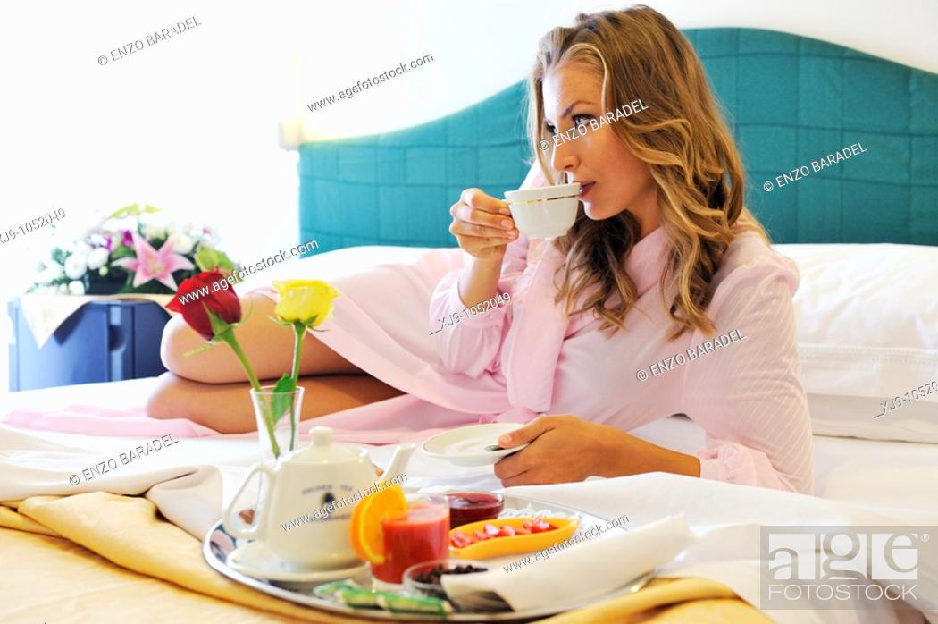 Stock Photo: Young woman on bed in hotel room.