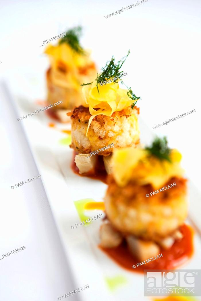 Stock Photo: Crab cakes with artichoke and fennel salad served with tomato sauce.