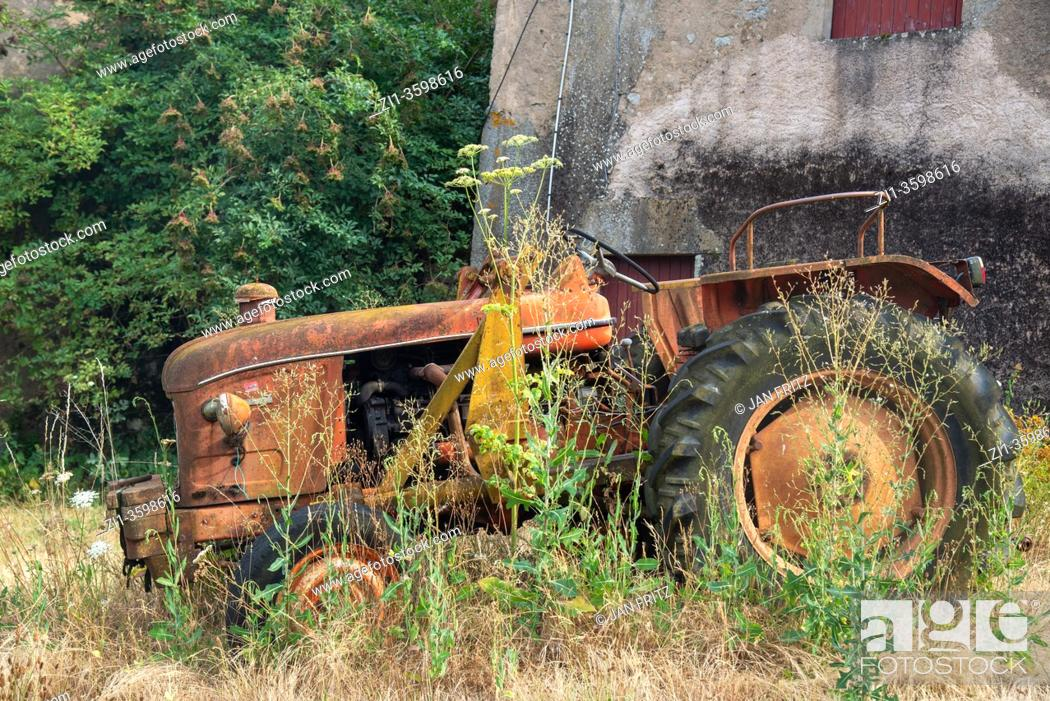 Imagen: old red tractor at farm in Bourgogne, France.