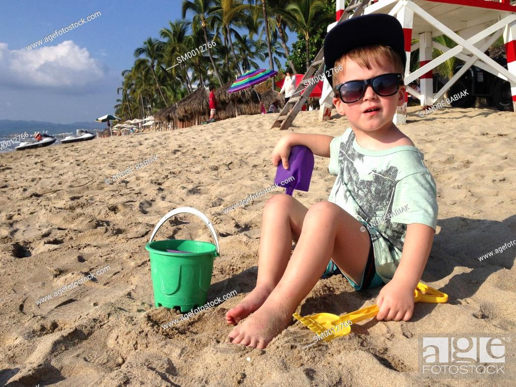 Stock Photo: Toddler boy child playing in the sand with toy bucket, shovel and rake at a beach in Mexico.