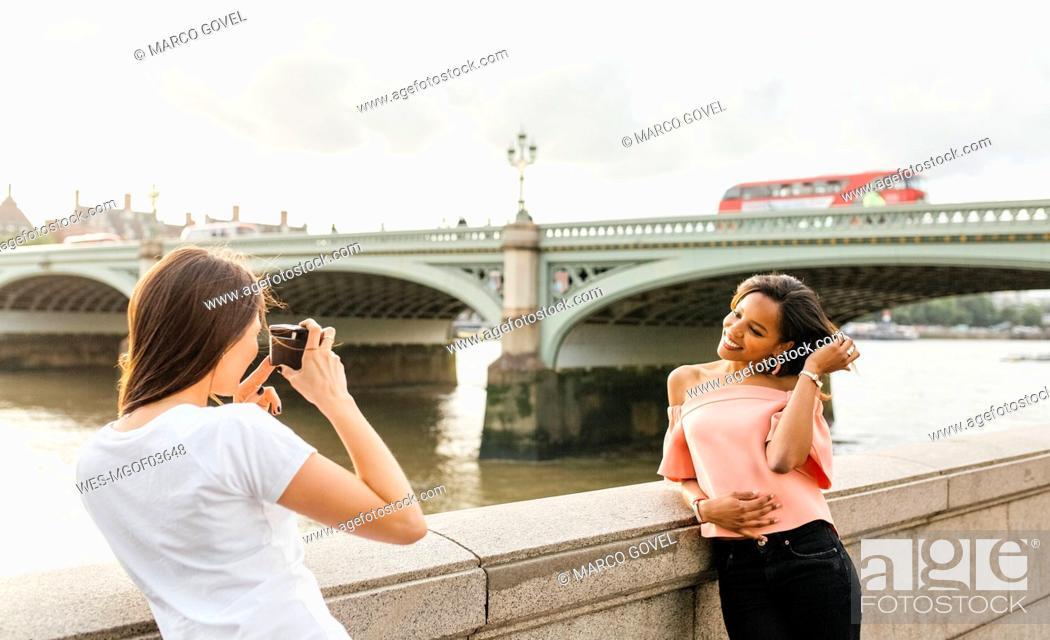 Imagen: UK, London, woman taking a picture of her friend near Westminster Bridge.