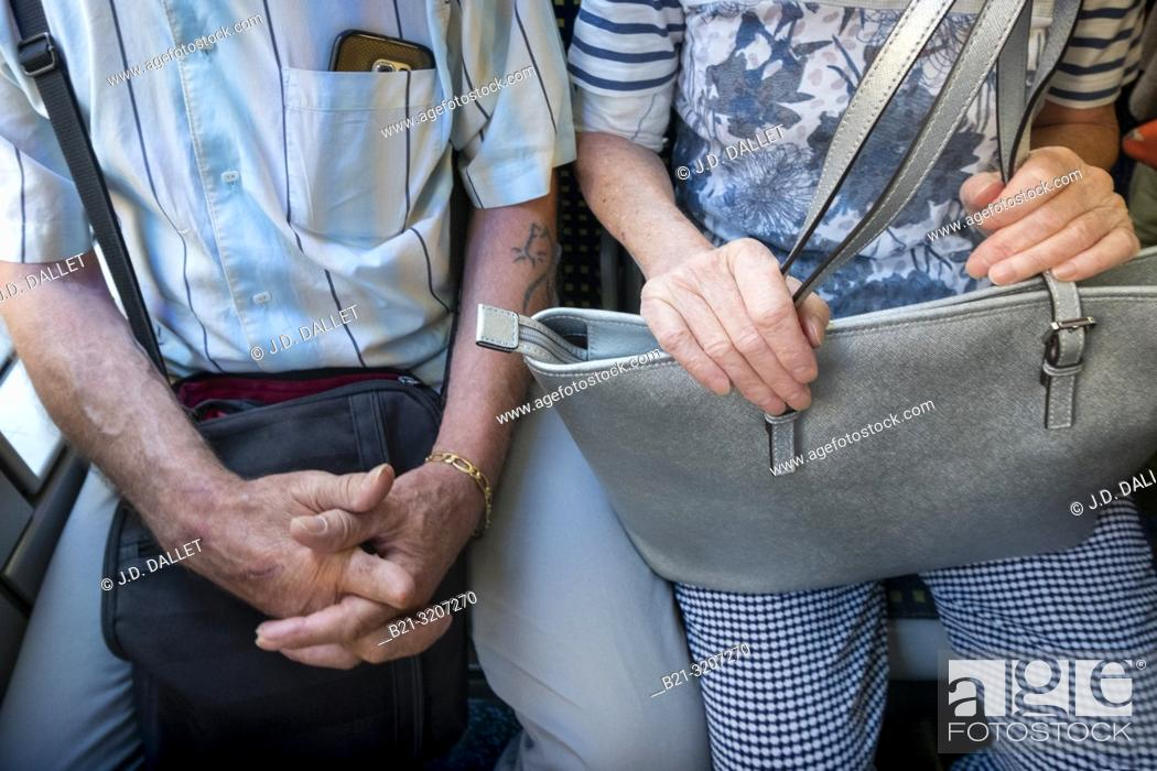 Imagen: Senior couple sitting in public transport.