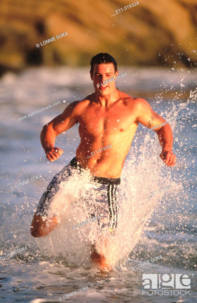 Stock Photo: 23 year old man jogging on beach.
